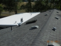 Completed TPO rubber roof on low slope joining a laminated sloped roof