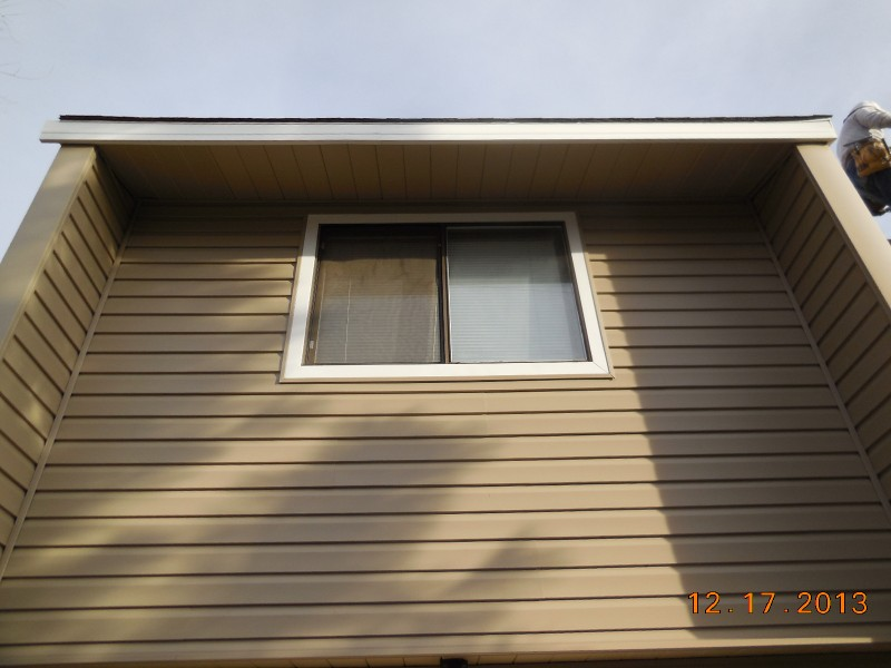 Dutch Lap vinyl siding covering parapet side walls and aluminum window trim wrap