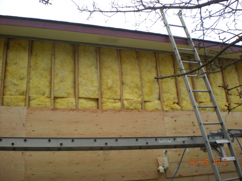 Inspecting insulation for moisture damage because of old LP siding prior to resheeting and residing with vinyl