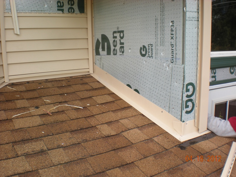 installing foam insulation board before vinyl siding and aluminum flashing at roof line for water protection and laminated roofing shingles