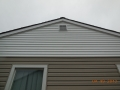 Installing two tone vinyl siding seperating house wall and gable wall and vent for contrast